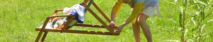 Kind klapt een ouderwetse strandstoel uit.