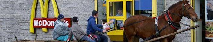 Mannen met paard en wagen halen bij het Drive-In loket van MacDonald een bestelling af.