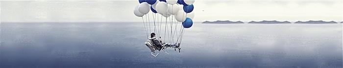 Een ligstoel hangt aan een tros ballonnen boven zee. In de ligstoel ligt een man comfortabel van een glas wijn te genieten. Hij heeft uitzicht op een eiland in de verte.