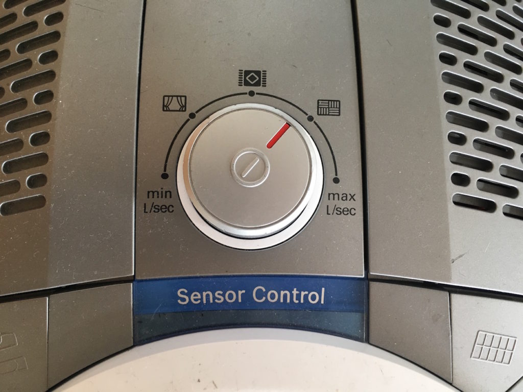 Detail van de stofzuiger waarop de start-stopknop niet direct te vinden is. Op deze afbeelding is wel te zien dat de draaiknop voor het vermogen tevens dienst doet als drukknop voor starten en stoppen.