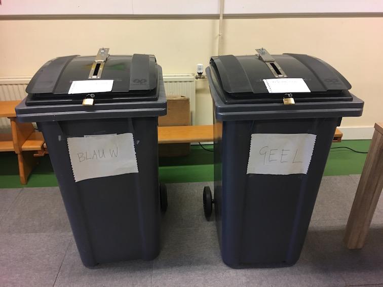 Twee stembussen met daarop handgeschreven briefjes met 'Gemeenteraad', 'Blauw' en 'Referendum', 'geel'.